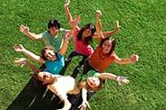 Six volunteers on a green grass field