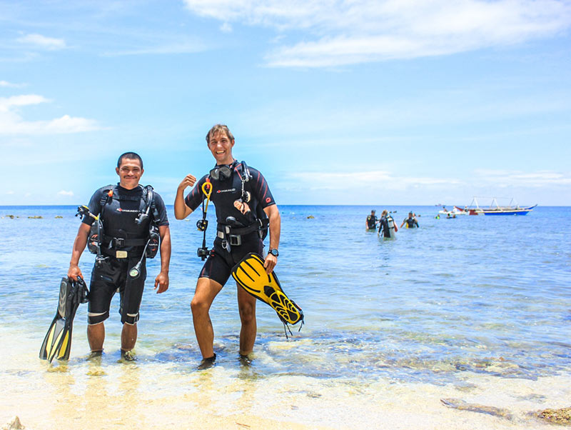 Divemaster coming out of the water with discover scuba participant